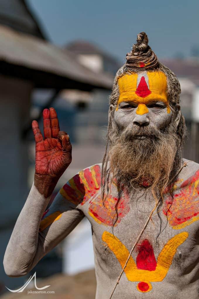 "A sadhu, or Hindu holy man, showing the ""om"" symbol with his right hand at Pashupatinath, Kathmandu, Nepal."