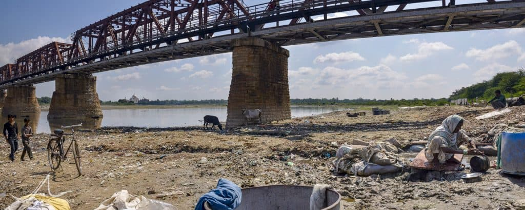 A poor woman from the dhobi, or clothes washing, caste, cleans pots along the waste-strewn banks of the Yamuna River at Dhobi Ghat, Agra; the famed Taj Mahal rises behind.