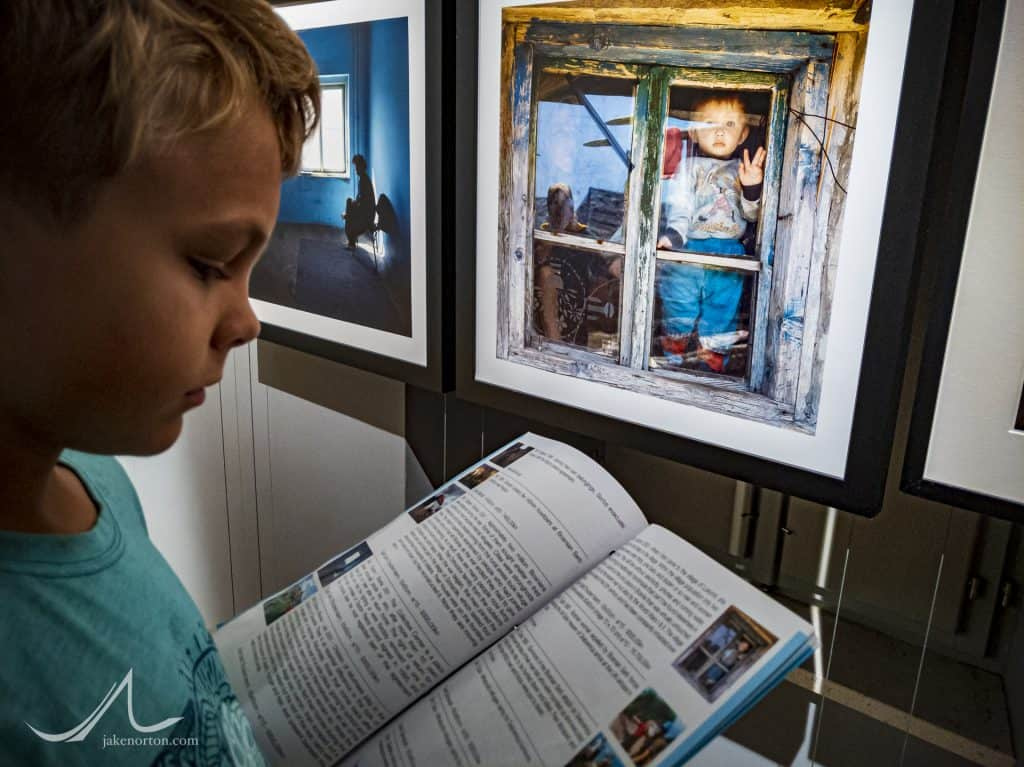 Ryrie Norton reads about the images on exhibit in the War Photos Exhibit, Dubrovnik, Croatia.