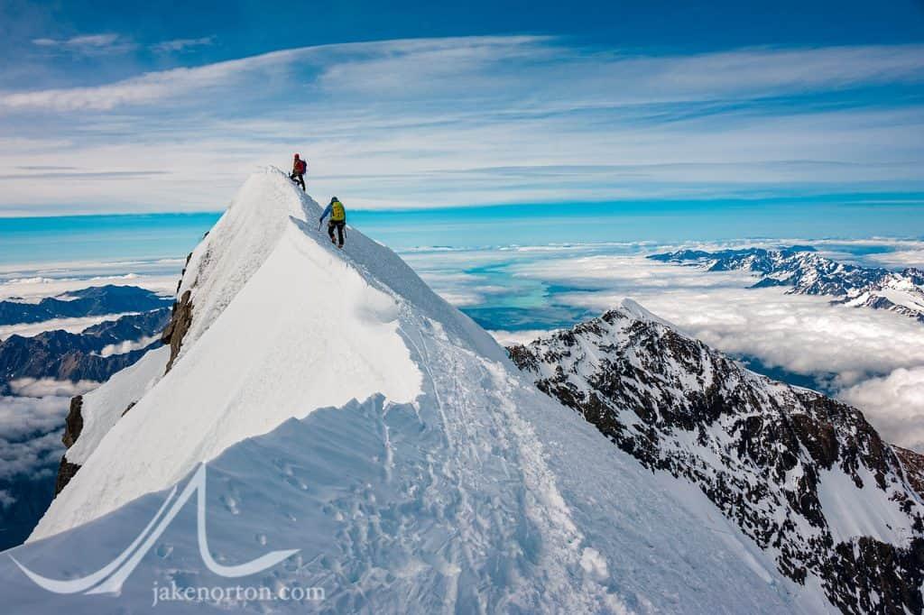 David Morton belays Charley Mace up to the steep summit of Aoraki (Mount Cook), New Zealand.