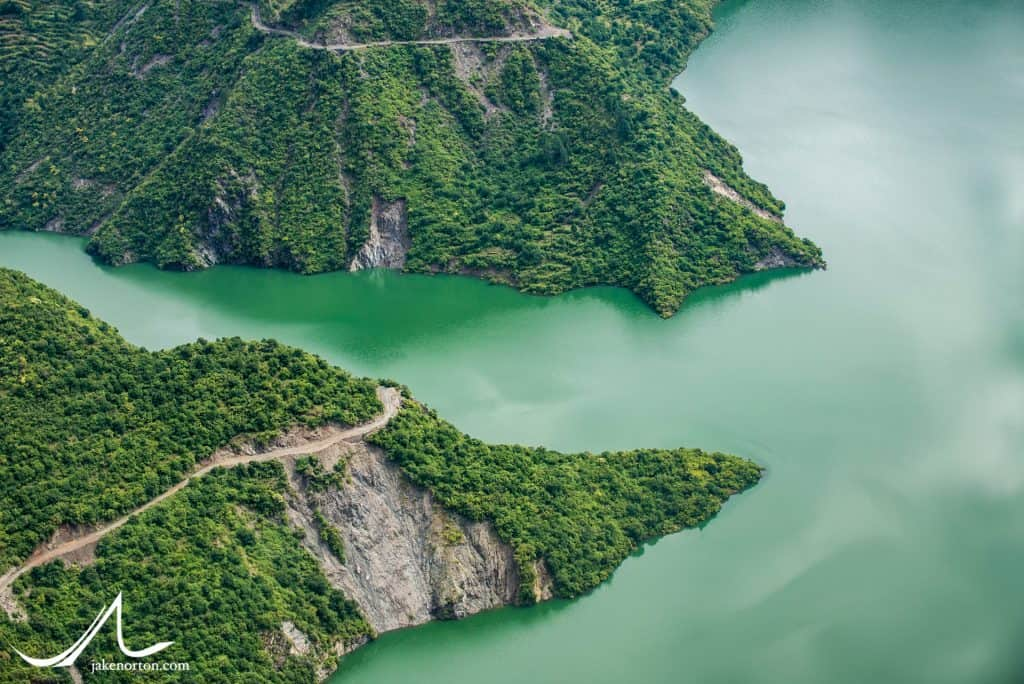 Roads scratch along the hillsides above the Tehri Lake, a manmade and controversial lake created by the Tehri Dam on the Bhagirathi River, which is the initial source river for the Ganges. After the dam, the Bhagirathi flows down to join the Alaknanda at Devprayag, and the Ganges River is born.