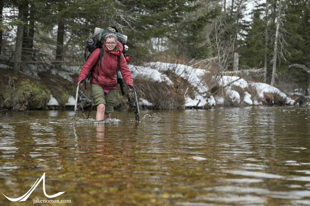 A student crosses the icy Swift River on Outback 2020.